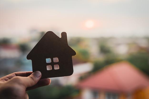 Modèle de maison en main d'agent de courtier d'assurance habitation ou en personne de vendeur.