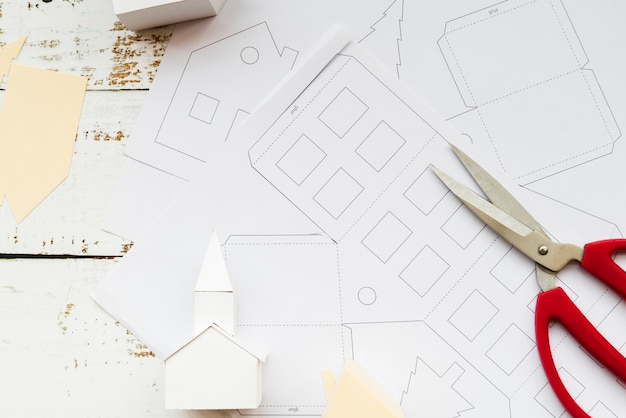 Modèle de maison à la main et des ciseaux sur du papier blanc sur la table en bois blanc