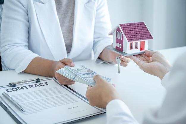 Modèle de maison en mains, l'agent immobilier explique le contrat commercial, le loyer, l'achat, l'hypothèque, un prêt ou une assurance habitation à l'acheteur professionnel.