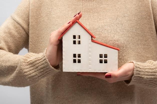 Modèle de maison en mains féminines
