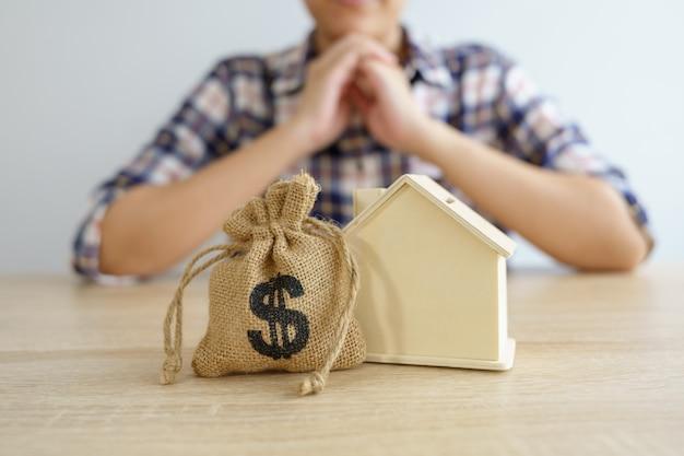 Un modèle de maison modèle est placé sur the hands of asian business girl.