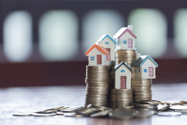 Modèle de maison sur la pile de pièces. concept pour échelle immobilière, hypothèque et investissement immobilier.