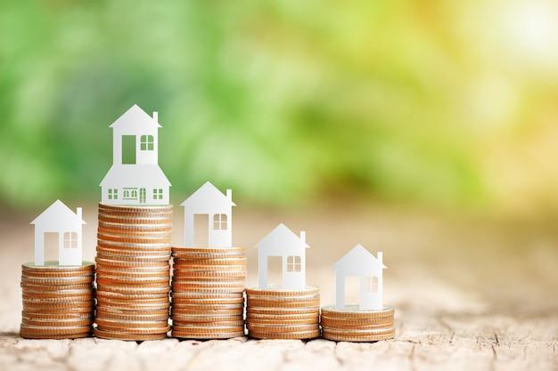 Modèle de maison sur pile de pièces pour épargner en vue d'acheter une maison