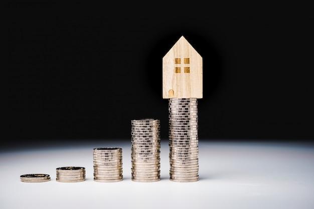 Modèle de maison et rangée de pièces de monnaie sur tableau blanc