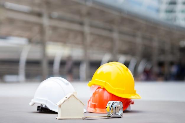 Modèle de maison, ruban à mesurer, casque de sécurité et construction ou
