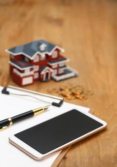 Modèle de maison, smartphone, calculatrice et pièces d'or sur table en bois