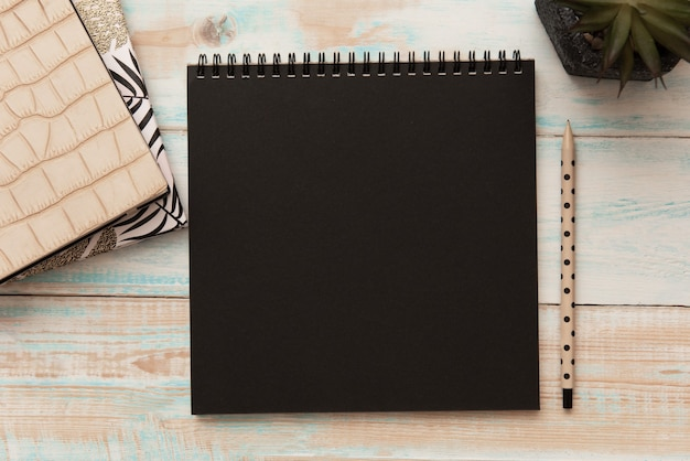 Modèle de maquette de bloc-notes en spirale avec papier noir, crayon et plante en pot sur un bureau en bois