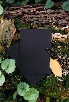 Modèle de maquette de papier artisanal noir sur le fond de la nature magique de la forêt