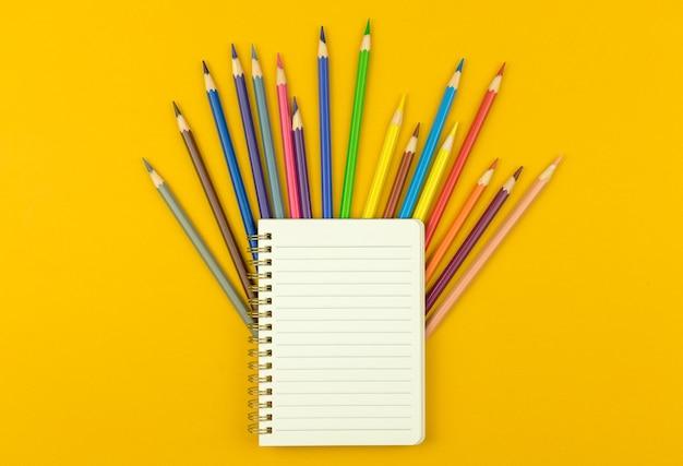 Modèle ou maquette de retour à l'école, bloc-notes avec crayons de couleur sur fond de bureau jaune, photo vue de dessus