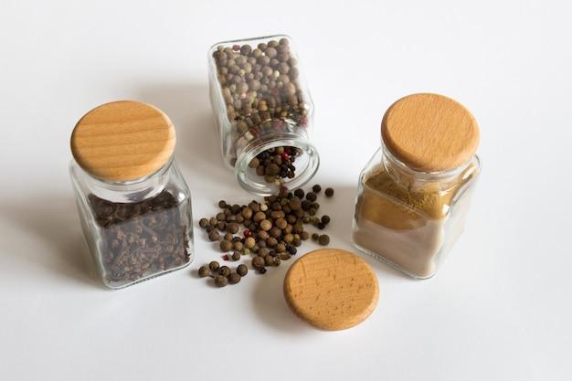 Modèle de maquette avec trois bocaux en verre bouteilles hermétiques avec bouchons en bois et épices herbes poivre noir