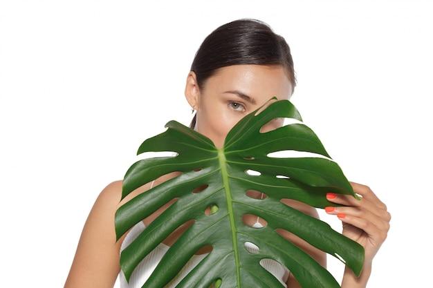 Modèle avec maquillage naturel et feuille verte isolé sur blanc. spa et bien-être.