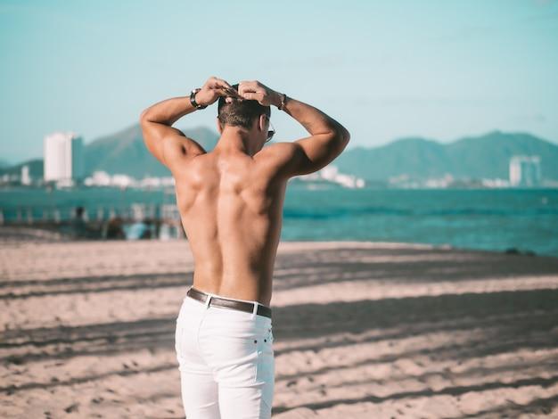 Modèle masculin à l'arrière. homme sur la plage