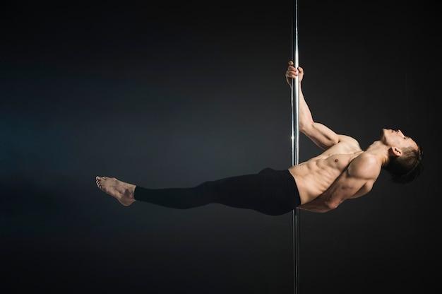 Modèle masculin attrayant effectuant une pole dance