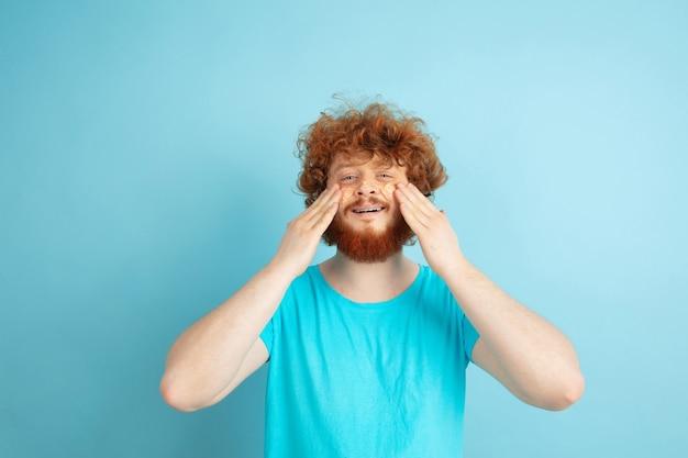 Modèle masculin aux cheveux roux naturels appliquant une crème hydratante, des huiles sur la peau du visage