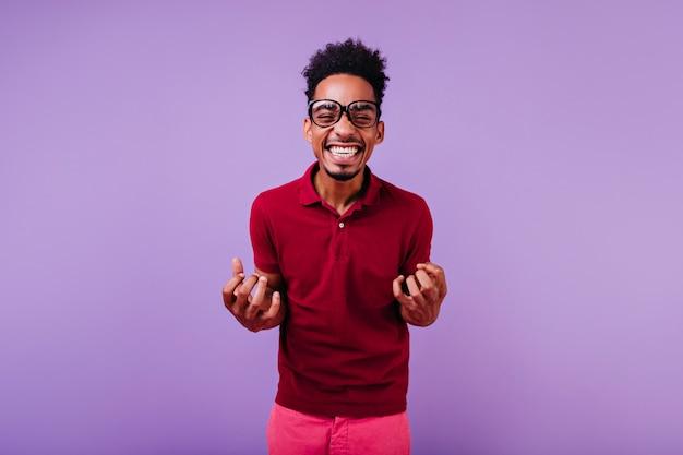 Modèle masculin bouclé aux cheveux courts en riant. guy africain inspiré dans des verres posant.