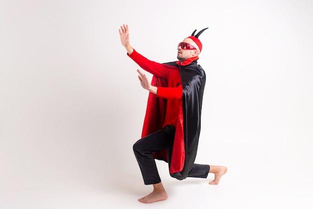 Modèle masculin en costume rouge noir halloween et lunettes de soleil avec chapeau et cornes posant