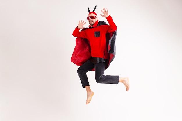 Modèle masculin en costume rouge noir halloween et lunettes de soleil avec chapeau et cornes sautant