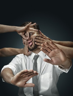 Un modèle masculin entouré de mains comme ses propres pensées sur un mur sombre