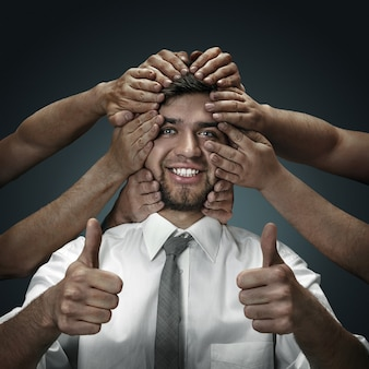 Un modèle masculin entouré de mains comme ses propres pensées ou problèmes sur un mur sombre