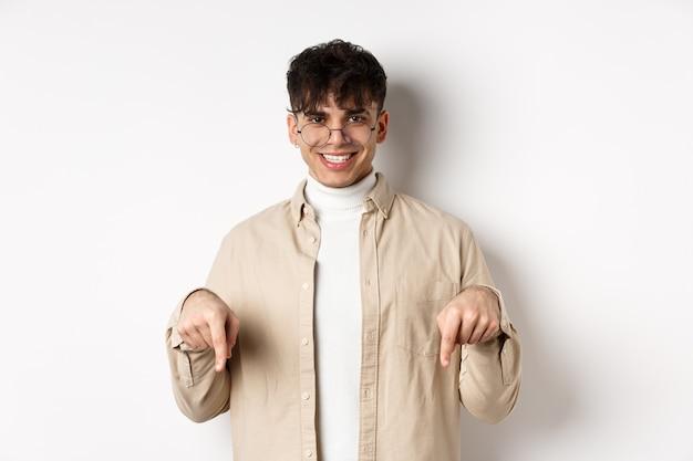 Modèle masculin hipster élégant dans des verres pointant les doigts vers le bas, souriant heureux devant la caméra, recommandant le produit, debout sur fond blanc.