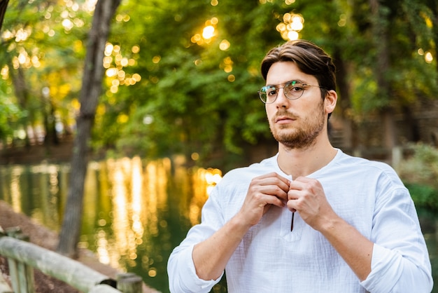 Modèle masculin avec des lunettes et une chemise blanche posant dans un parc avec floue.