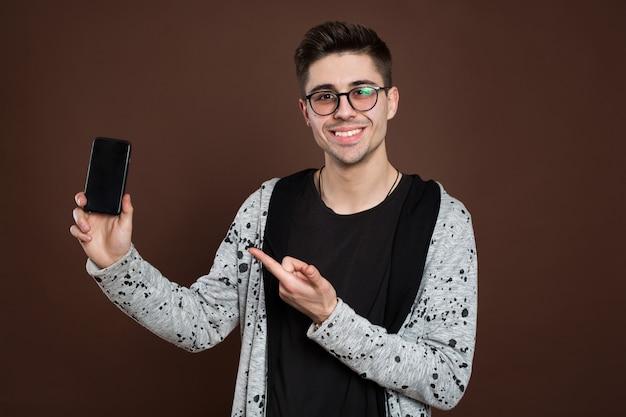 Modèle masculin montrant le smartphone à la caméra, isolé sur fond marron