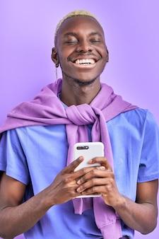 Modèle masculin noir africain avec appareil, utiliser un smartphone, discuter avec un ami, envoyer un message et partager des nouvelles, isolé sur un espace violet, sourire à la caméra