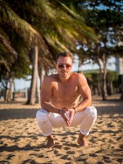Modèle masculin sur la plage au coucher du soleil