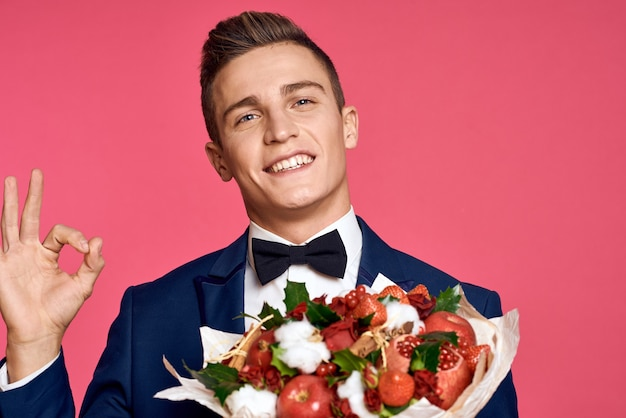 Modèle masculin posant dans un costume classique en studio sur un fond avec un bouquet de fleurs