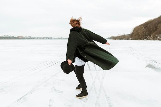 Modèle masculin posant dans des vêtements d'hiver à la lumière du jour