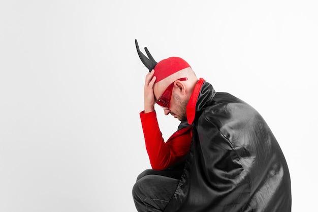 Modèle masculin de race blanche en costume rouge noir halloween et lunettes de soleil avec chapeau et cornes posant sur blanc.