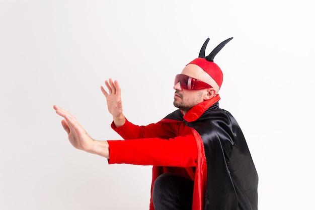 Modèle masculin de race blanche en costume rouge noir halloween et lunettes de soleil avec chapeau et cornes posant sur fond blanc.