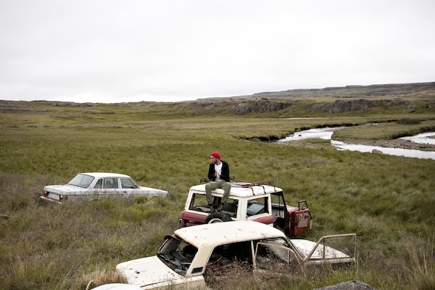 Modèle masculin en tenue cool sur le dessus de la voiture dans la cour de ferraille