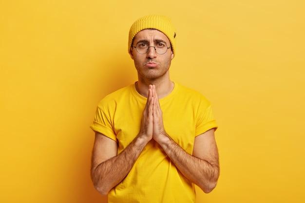 Modèle masculin triste avec une expression de supplication, garde les paumes ensemble, se sent coupable, demande pardon