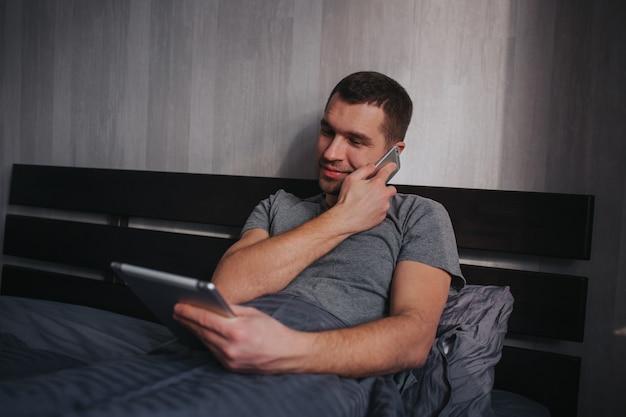 Le modèle masculin utilise la tablette et le téléphone en même temps. un homme au lit le matin. travail à la maison.