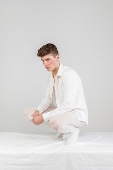 Modèle masculin de vue de face posant avec un fond blanc