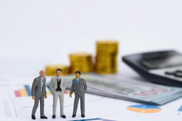 Modèle miniature de gens d'affaires de co-investissement debout sur le graphique de rapport d'entreprise