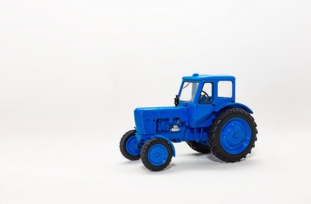 Modèle miniature d'un jouet tracteur bleu isolé sur fond blanc