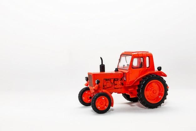 Modèle miniature d'un jouet tracteur rouge isolé sur fond blanc