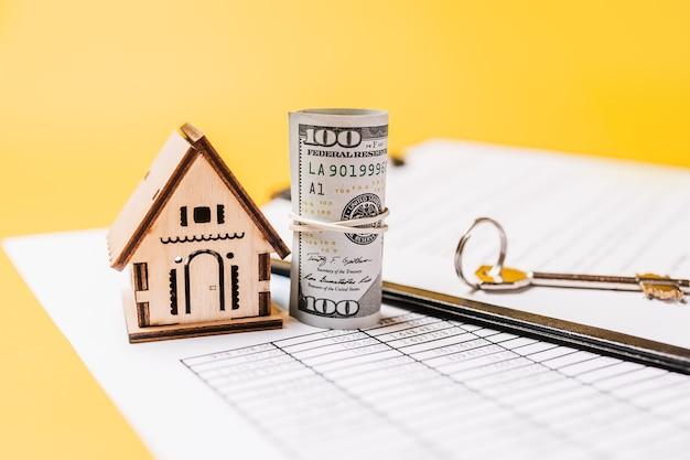Modèle miniature de maison et argent sur documents