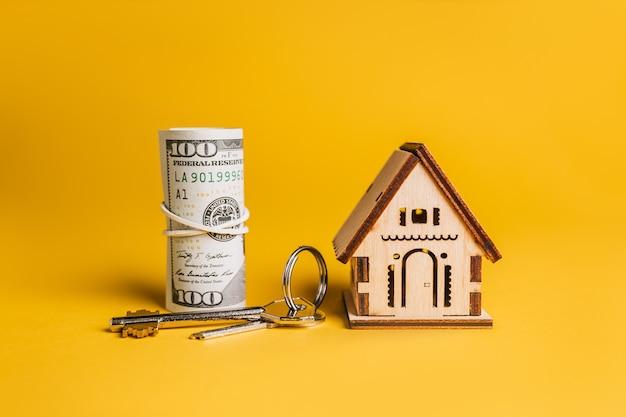 Modèle miniature de maison, clés et argent sur une surface jaune. investissement, immobilier, maison, logement