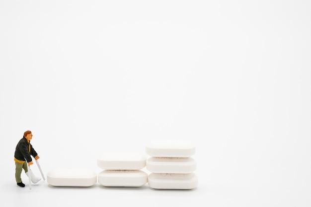 Modèle miniature de vieil homme jambes brisées autour avec des pilules de médecine pharmaceutique