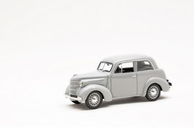 Modèle miniature d'une voiture rétro gris jouet sur une surface blanche