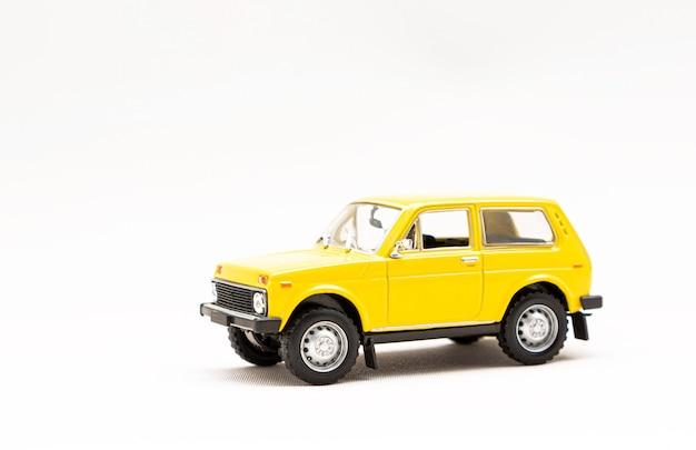 Modèle miniature d'une voiture rétro jaune isolée sur une surface blanche
