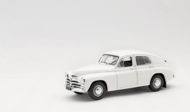 Modèle miniature d'une voiture rétro jouet blanc sur fond blanc.