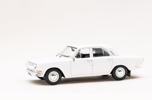 Modèle miniature d'une voiture rétro jouet blanc sur une surface blanche