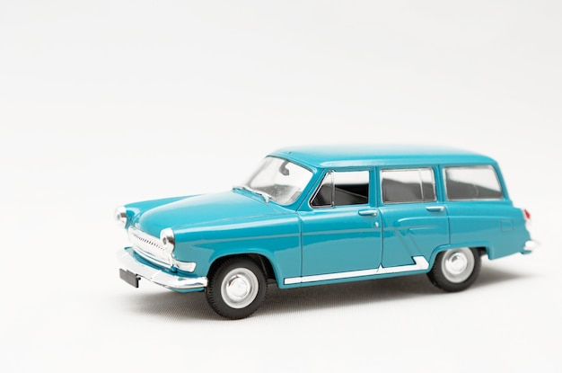 Modèle miniature d'une voiture rétro jouet bleu sur fond blanc.