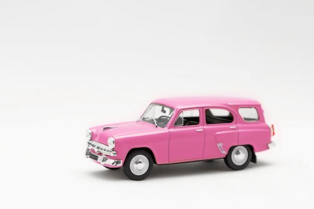 Modèle miniature d'une voiture rétro jouet rose sur fond blanc.