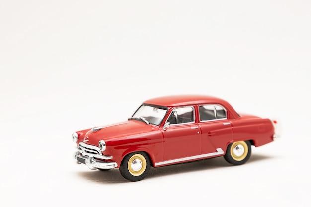 Modèle miniature d'une voiture rétro rouge jouet sur une surface blanche
