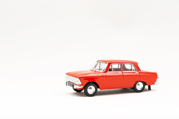 Modèle miniature d'une voiture rétro rouge sur une surface blanche